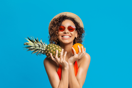 Tropical fruits season. Positive girl holding fresh orange and pineapple, blue studio background