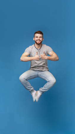 Enjoy life moments. Joyful redhaired man jumping in air, demonstrating thumbs up gesture, blue studio background, full length, free space