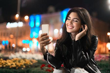 Happy girl enjoying playlist songs on phone, walking at night in the city 写真素材