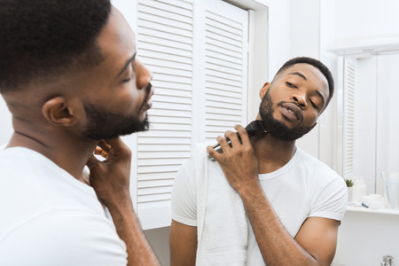Afro man shaving his beard looking in mirror at bathroom. Mans daily care concept Stok Fotoğraf