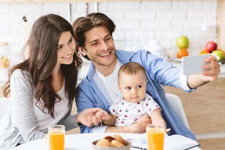 Family selfie. Millennial parents photographing themselves with baby son, dining in kitchen