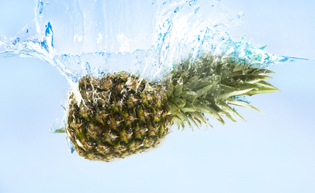 Fresh ripe pineapple falling in water with splash, blue background