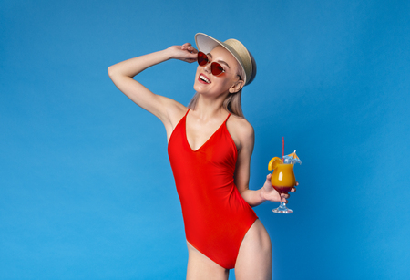 Summer Relax. Millennial Blonde In Red Swimsuit Enjoying Tropical Cocktail, blue studio background