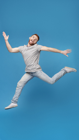 Funny millennial guy jumping in air and fooling on blue background, full length, empty space Stok Fotoğraf