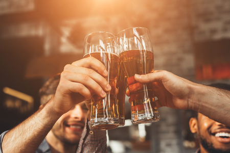 Men Drinking Draft Beer And Clinking Glasses At Pub, Closeup
