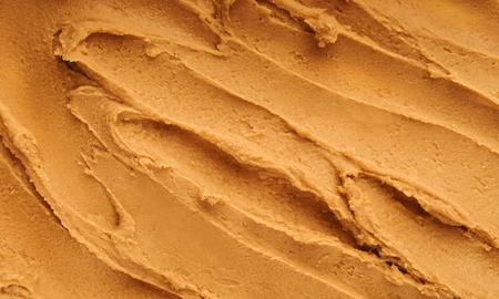 Burro di arachidi con texture di sfondo, vista dall'alto. Concetto di sfondo alimentare