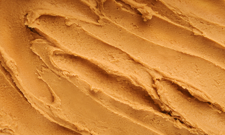 Peanut butter textured background, top view. Food background concept