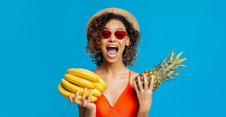 Tropical summer fruits. Emotional black girl holding bananas and pineapple, blue studio background