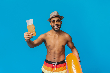 Time for Trip. Cheerful black guy in summer wear holding passport with tickets and inflatable ring, orange studio background