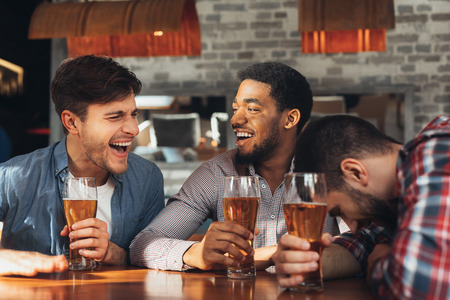 Friends Meeting. Men Drinking Beer And Talking, Having Rest In Bar Together