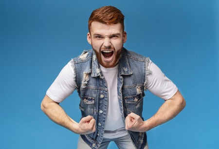 Young furious muscular redhaired man screaming loudly at camera, blue studio background Stock Photo