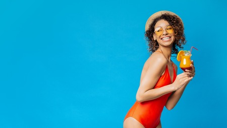 Enjoying summer rest. Cheerful black girl in swimsuit drinking tropical cocktail, blue panorama background with empty space Stockfoto