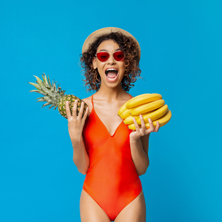 Joyful african woman holding fresh pineapple and bananas, blue studio background