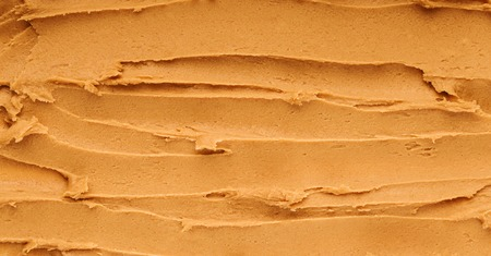 Peanut butter textured background, top view. Food allergy concept