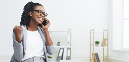 Excited African Woman Talking On Phone, Celebrating Success In Office, Free Space