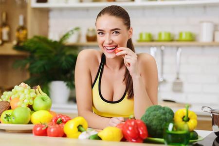Gezonde levensstijl. Sportieve vrouw staande in de buurt van groenten en fruit in de keuken