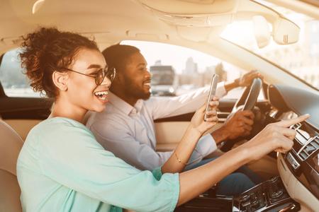 Viajar juntos. Pareja afroamericana con sistema de navegación, conducción de coche Foto de archivo