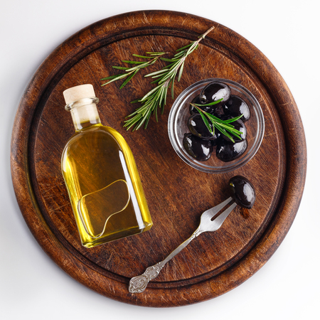 Olive oil and black olives in bowl on wooden board over white background, top view. Greek appetizers concept