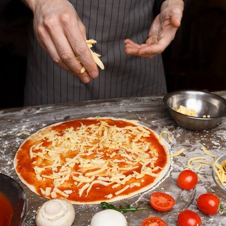 Italian Cuisine. Cook Hand Adding Grated Cheese To Pizza At Pizzeria