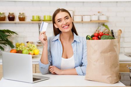 Online-Einkauf von Lebensmitteln. Frau mit Kreditkarte, Laptop und Gemüse in Bastelpapiertüte