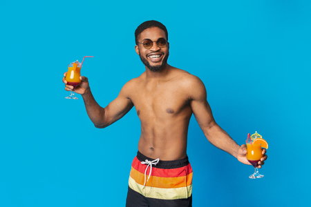 Pool party bartender. Cheerful black guy with two fresh summer cocktails, blue studio background