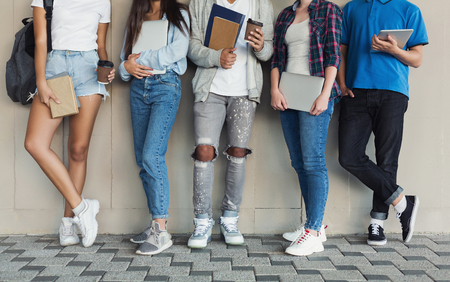 Cool youth time. Teenagers standing at campus wall, holding devices and books, panorama with free space
