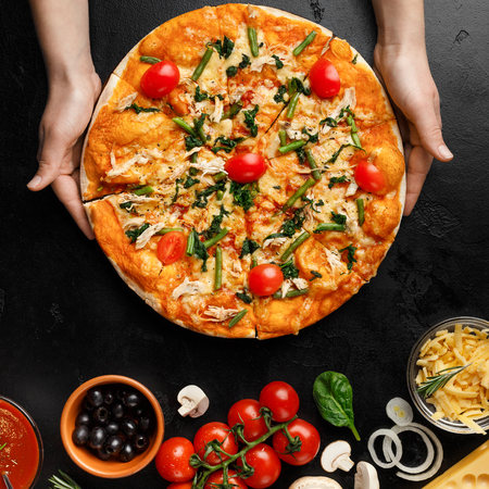 Woman Putting Homemade Pizza On Table With Various Ingredients Nearby, Crop