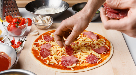 Chef Cooking Pizza. Hands Putting Salami On Pizza Base, Panorama