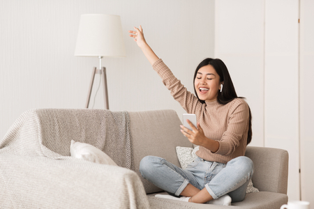 Happy Girl Enjoying Music In Airpods And Singing Favourite Song, Relaxing On Sofa