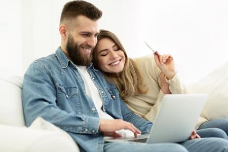 ¡Tan fácil! Pareja milenaria haciendo compras en línea en Internet, usando laptop