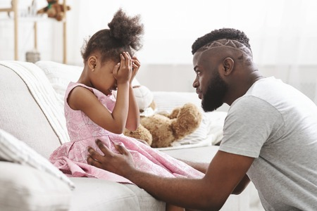 Loving african american dad comforting crying daughter, supporting little stressed girl in tears, giving empathy protection at home