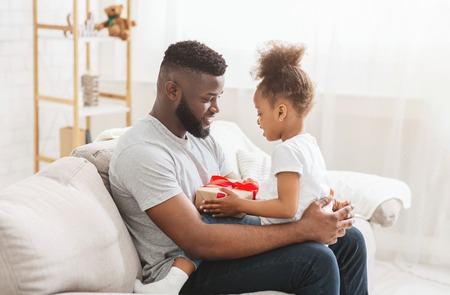 Lovely family moments. African american man sitting with his little daughter with gift box, free space Standard-Bild
