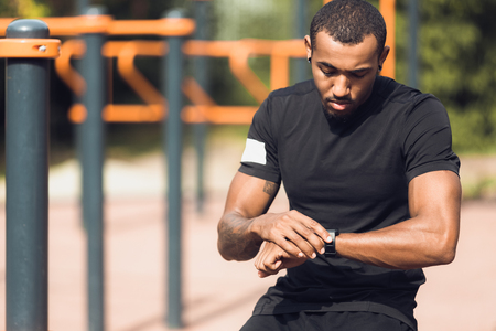 Sporty Man Checking His Performance On Fitness Smartwatch After Workout Outdoors Stock Photo
