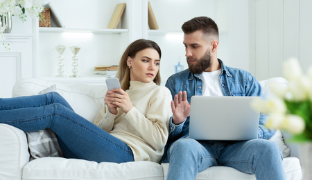 Woman Spying Husbands Laptop, Sitting Together On Sofa With Devices