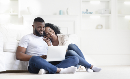 Planning summer vacation. Cute african american couple searching hotel and resort online, using laptop on floor at home, free space Stock fotó