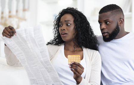 Shocked millennial african american couple reading leaflet before taking contraceptive pills, sitting on couch at home, free space