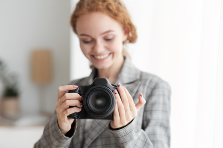 Female Photographer Taking Photo With Professional Photo Camera In Her Office Stock Photo