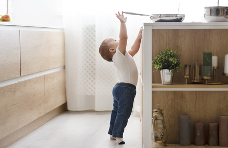 Child safety at home concept. Little baby reaching for hot pan on stove in kitchen, empty space