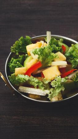 Fresh salad with vegetable and pineapple, wooden rustic background, vertical panorama Stock Photo