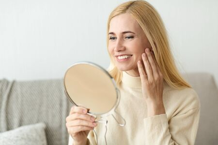 Facial Care. Smiling Mature Woman Satisfied With Her Nature Beauty, Looking At Mirror