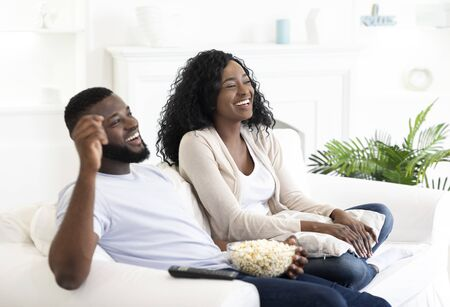 Black millennial couple watching tv, sitting on couch with popcorn at home, free space