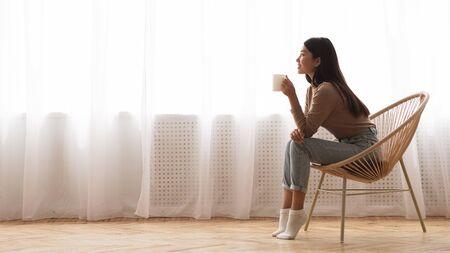 Meisje genieten van koffie in de ochtend, zittend in een leunstoel voor raam, zijaanzicht