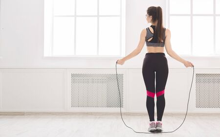 Sporty girl jumping over the skipping rope in front of big windows in studio, panorama, back view, copy space