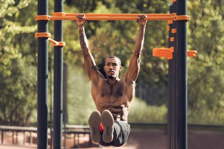 Afro Sporty Man Doing L-Sit Exercise On Horizontal Bar Outdoors Imagens