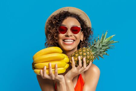 Enjoying summer time. Happy african woman hugging fresh tropical fruits, blue studio background