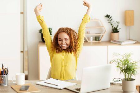 Diseñador creativo que se extiende delante de la computadora portátil, trabajando en la oficina