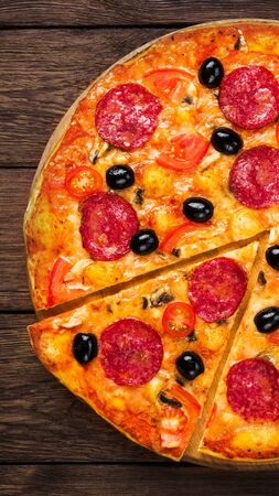 Thin pizza with salami, cherry tomatoes and black olives at wooden table background, vertical panorama Stock Photo