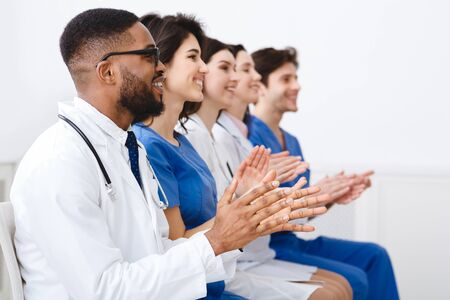 Medical Education. Doctors And Interns Clapping Hands At Conference, Looking At Empty Space
