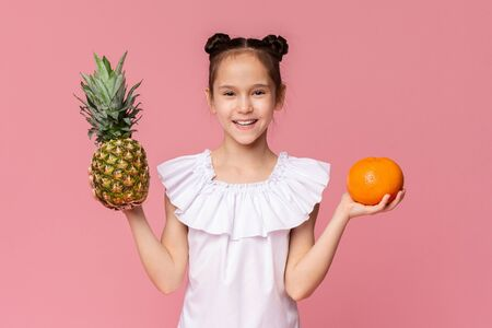 Seasonal snacks. Cute little girl holding fresh pineapple and orange on pink studio background Banque d'images - 124592196