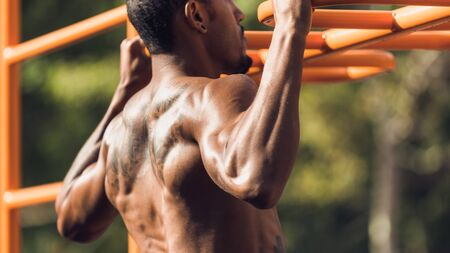 Muscular Afro Man Doing Pull Ups On Horizontal Bar, Working Out In Morning, Closeup Фото со стока